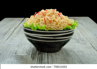 Instant noodle in the bowl on wooden background
