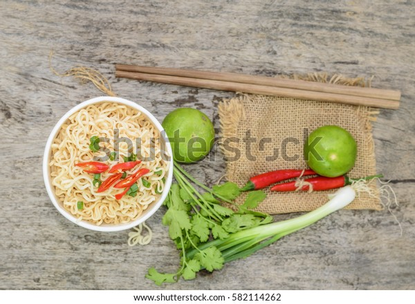 instant noodle with fresh vegetables on wood