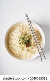 Instant noodle and seasoning in white bowl with chopstick
