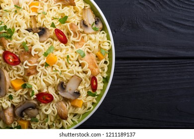 Instant noodles in bowl with chili peppers, mushrooms , chicken and carrots