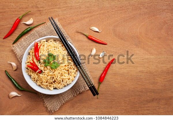 Instant noodles in the bowl with pepper and garlic on brown wooden background. Top view and Copy space
