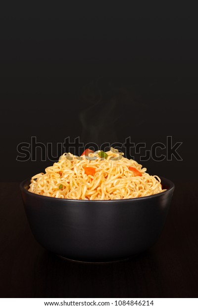 Instant noodles in the bowl with tomato and onion on wooden table