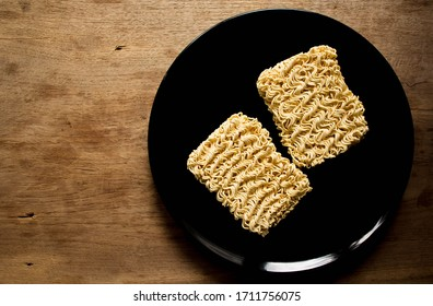 Instant noodles or dry noodles circle isolated a black plate on wooden background. The best food during bad economic times.