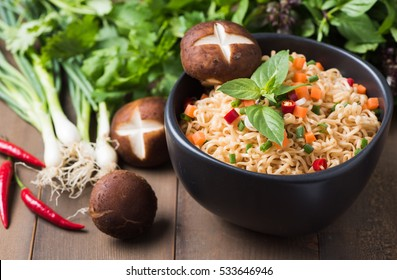 instant noodles with fresh vegetables on wood background, fast food