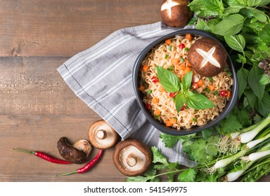 instant noodles with fresh vegetables on wood background, fastfood