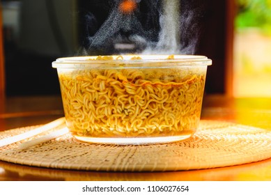 Instant noodles in glass bowl with steam. Concept of little nutritional value food.