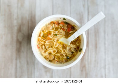 instant noodles, noodle soup in a cup, view from above. Instant noodles are sold in a precooked and dried noodle block, with flavoring powder and/or seasoning oil.