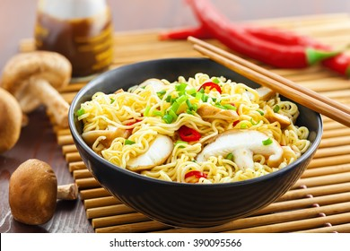 Instant noodles with shiitake mushrooms, pepper and onion in a bowl, Asian meal on a table