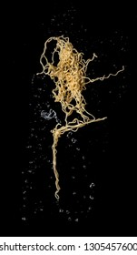 Instant noodles with soup splash or explosion flying in the air over dark background