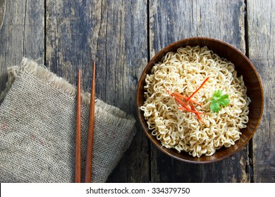 Instant noodles in wooden bowl on wood background