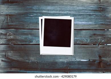 Instant photo frame on wood background.