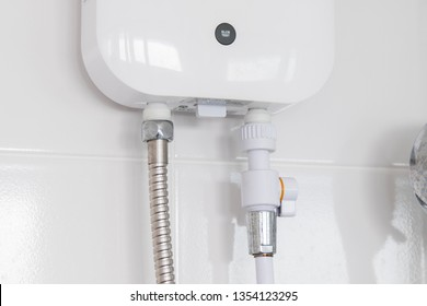 Instant tankless electric water heater installed on white tile wall with input and output pipe/outlet and elcb safety breaker system