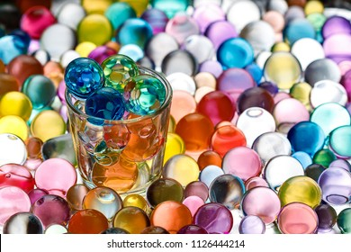 instead of alcohol poured into a glass of hydrogel balls of different colors, contrasting colored beads