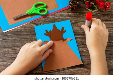 Instruction step 5. Merry greeting card with a Christmas deer on a wooden table. Handmade. Children's creativity project, crafts, crafts for kids.