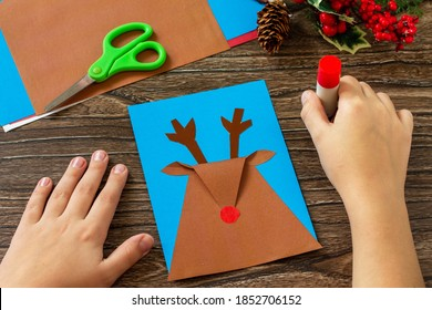 Instruction step 6. Merry greeting card with a Christmas deer on a wooden table. Handmade. Children's creativity project, crafts, crafts for kids.