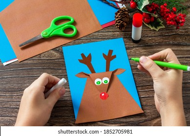 Instruction step 7. Merry greeting card with a Christmas deer on a wooden table. Handmade. Children's creativity project, crafts, crafts for kids.