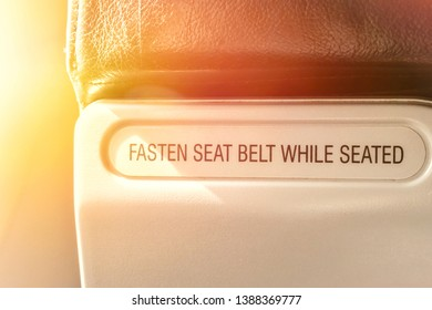 instructions or rule text or sentences on the plane notify or remind to passengers  about the fasten seat belt while seated