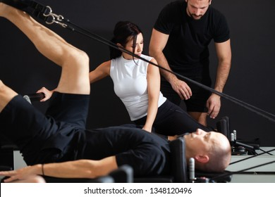 Instructor Assisting Woman On Reformer Machine In Gym while the other men pulling out reformer band,Pilates concept