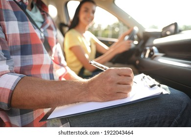 Instructor with clipboard writing result of exam in car, closeup. Driving school