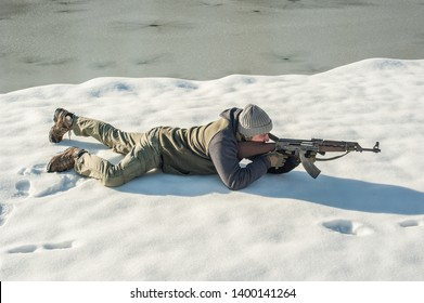Instructor demonstrate body position of combat rifle shooting at winter deep snow. Advanced fighting tactical shooting courses on outdoor shooting range