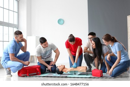Instructor demonstrating CPR on mannequin at first aid training course