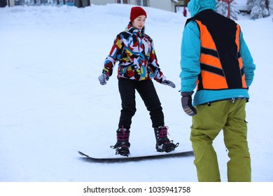 Instructor giving snowboard lessons for young woman at snowy resort. Winter vacation