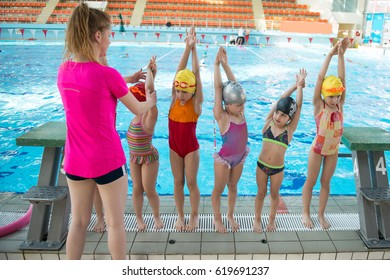Instructor and group of children doing exercises near a swimming pool