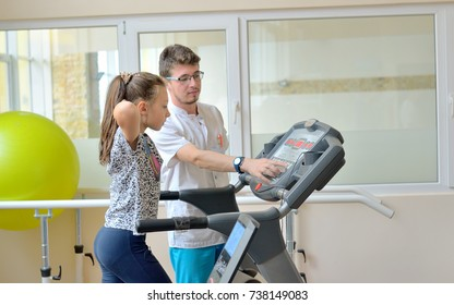 Instructor in gym with little girl on treadmill
