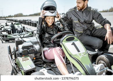 Instructor with happy young woman driver wearing protective helmet before the race on the go-kart track outdoors