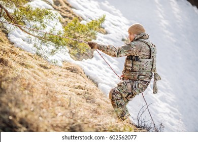 Instructor helping another soldier to climb up the hill. Two military men in the background of a winter hill. People and military concept