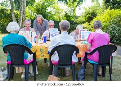 Instructor helping a group of senior retired ladies at art class seated around a table painting outdoors in a garden or park.