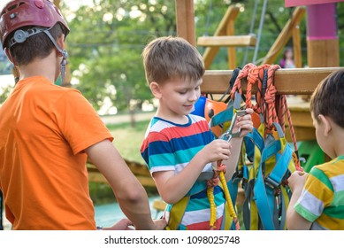 Instructor helping little boy to put helmet and safety belts to participate in rope park. Active healthy leisure time spending concept with children.