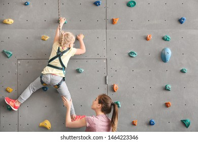 Instructor helping little girl to climb wall in gym