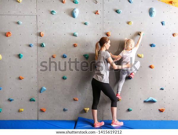 体育館の壁に登る少女の手伝いをするインストラクター