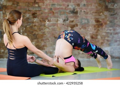 Instructor helps to do yoga exercise on an stretching
