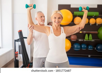With instructor. Mature man instructing blonde woman in gym