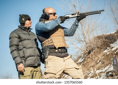 Instructor on shooting range teaches his student how to shoot with shotgun. Combat pump gun shooting training. Firearm shooting and weapons training