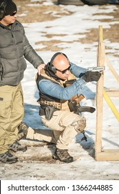 Instructor on shooting range teaches his student tactical gun shooting behind and around cover or barricade. Firearm shooting and weapons training.
