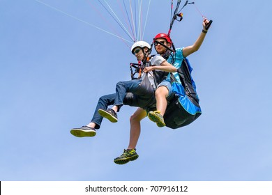 Instructor and paraglider boy floating in blue sky