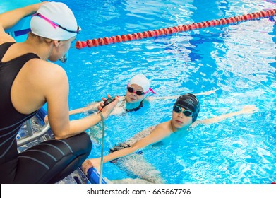 The instructor in the pool with a stopwatch marks the time at the start of the small swimmers