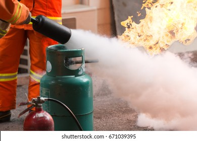 Instructor showing how to use a fire extinguisher. Gas tanks with fire. during training