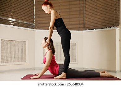 Instructor stretches students neck at yoga exercise