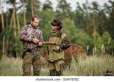 Instructor with woman hunter aiming rifle at firing