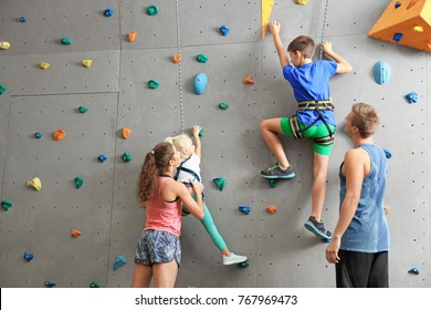 Instructors helping children climb wall in gym