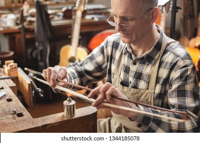Instrument maker inside a rustic workshop is skillfully heating the hair of a violin bow