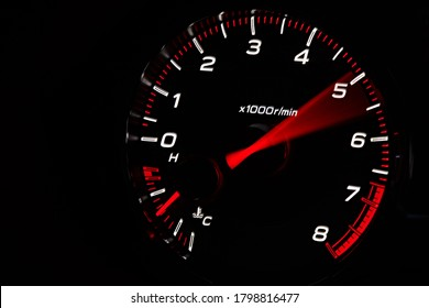 Instrument panel with tachometer and fuel level temperature engine, Close up image of illuminated car dashboard. Red arrow moving