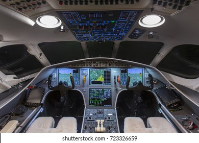 Instrument panels in cockpit of a very modern private business jet at night