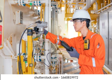 Instrument technician operator calibrate pressure transmitter with hand held calibrator on offshore oil and gas central processing platform.