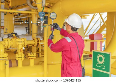 Instrument technician perform test and calibrate pressure transmitter compare with standard test gauge, oil and gas industrial.