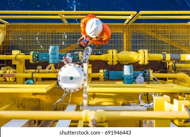 Instrumentation operation technician calibrating oil field instrument, Coriolis flow meter and actuated control valve on offshore oil and gas platform.